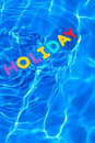 Word HOLIDAY floating in a swimming pool Stock Photography