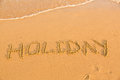Word holiday on the yellow sandy beach text Stock Image
