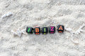 Word Ibiza is made of multicolored letters on snow-white sand against the blue sea Royalty Free Stock Photo