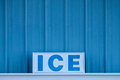 Word ICE in capital letters on sign in front of cold blue metal Royalty Free Stock Photo