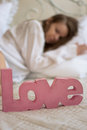 Word love bed next to girl blur Stock Photos