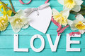 Word love heart and spring flowers on turquoise painted wooden background selective focus Royalty Free Stock Photos