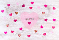 Word Love with paper Hearts shaped Valentines Day on white wooden background