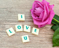 The word love and pink roses on table Stock Images
