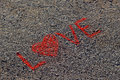 Word LOVE written on the asphalt, ground. Red color of chalk.