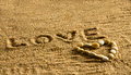 Word love written on a beach with the shape of a heart below Royalty Free Stock Images