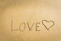 Word Love written on the sand heart drawn message romantic symbol concept Royalty Free Stock Photo