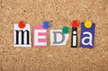 The word media in cut out magazine letters pinned to a cork notice board with multicolored drawing pins Royalty Free Stock Photos