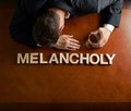 Word melancholy and devastated man composition made of wooden block letters middle aged caucasian in a black suit sitting at the Royalty Free Stock Image