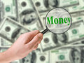 Word Money, magnifying glass in hand Royalty Free Stock Photography