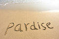 Word pardise drawn on the beach and sea wate Stock Photo