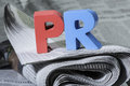 Word pr on newspaper wooden letters Royalty Free Stock Photos