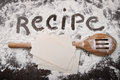 Word recipe written in white flour and spatula on wood wooden table Royalty Free Stock Photo