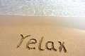 Word relax drawn on the beach and sea wate Royalty Free Stock Photo