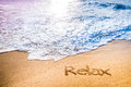 The word relax written into the sand on a tropical sandy beach in paradise waves are just about to wash away Royalty Free Stock Image