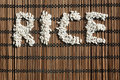 Word rice written with rice grains on a wicker placemat Stock Photography