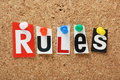 The word rules n cut out magazine letters pinned to a cork notice board Stock Image
