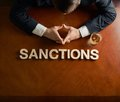 Word sanctions and devastated man composition made of wooden block letters middle aged caucasian in a black suit sitting at the Royalty Free Stock Image