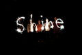 The word shine written with sparklers against a black background Royalty Free Stock Photo