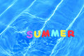 Word summer floating in a swimming pool Stock Image