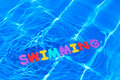 Word SWIMMING floating in a pool Royalty Free Stock Photo