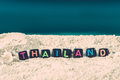 Word Thailand is made of multicolored letters on snow-white sand against the blue sea Royalty Free Stock Photo