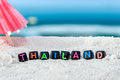 Word Thailand is made of multicolored letters on snow-white sand against the blue sea. Royalty Free Stock Photo