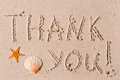 Word of thank you to sand or seashells the wet Stock Image