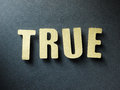 The word true on paper background in cut out letters Stock Image
