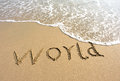 Word world drawn on the beach and sea wate Royalty Free Stock Images