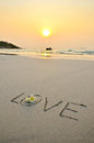 Wording love in sand handwritten on the beach and flower sunset Royalty Free Stock Images