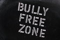 The words bully free zone in chalk stencil letters on a well used blackboard Royalty Free Stock Photography