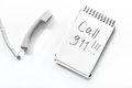 The words Call 911 written in a notebook near phone handset on isolated white background top view Royalty Free Stock Photo