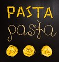 Words pasta made of cooked spaghetti and dry pasta on the black background with frame of country Italy written by chalk Royalty Free Stock Photo