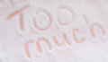 The words too much written in sugar grains. Overhead view. Royalty Free Stock Photo