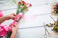 Work of florist hands tying carnation bouquet with pink silk ribbon Stock Photography