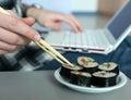 Work and Food Man working on Laptop taking Sushi Royalty Free Stock Photo