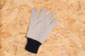 Work glove on plywood closeup of a single a a piece of strand board sheathing Stock Photos
