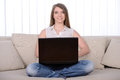 Work at home young beautiful woman working with a laptop sitting on sofa Royalty Free Stock Image