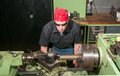 At work on a lathe machinist cutting piece of brass in the Stock Photo