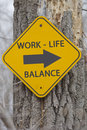 Work life balance this way sign on a tree in the woods making a great concept Royalty Free Stock Images