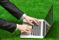 Work outdoors and businessman topic: human hands show the gestures in a black suit and an open notebook on a background of green g Royalty Free Stock Photo