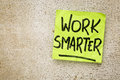 Work smarter reminder on a green sticky note against rustic barn wood p productivity concept Stock Image