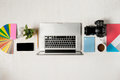 Work space for photographer, graphic designer. Flat lay of laptop, camera, colorchart, digital tablet, coffee cup, book, pencil o