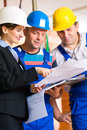 Work team on construction site controlling floor plan or architect and builder or worker with helmets or having discussion of or Royalty Free Stock Photos