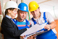 Work team on construction site controlling floor plan or architect and builder or worker with helmets or having discussion of or Stock Photography