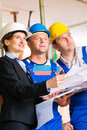 Work team on construction site controlling floor plan or architect and builder or worker with helmets or having discussion of or Stock Photos