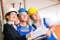 Work team on construction site controlling floor plan or architect and builder or worker with helmets or having discussion of or Royalty Free Stock Photography