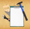 Work tools and clipboard over rough brown paper background Royalty Free Stock Photos