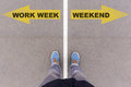 Work week vs weekend text arrows on asphalt ground, feet and sho Royalty Free Stock Photo